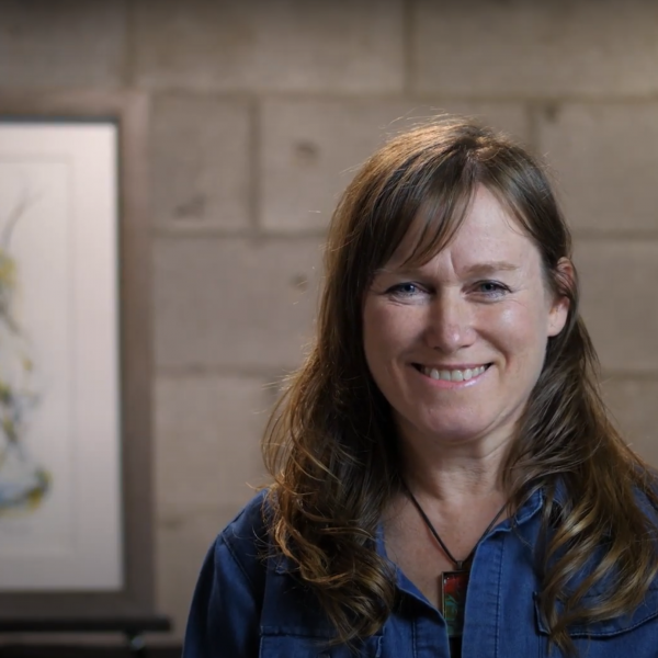 A photo of artist Catherine Luce smiling in front of her painting.