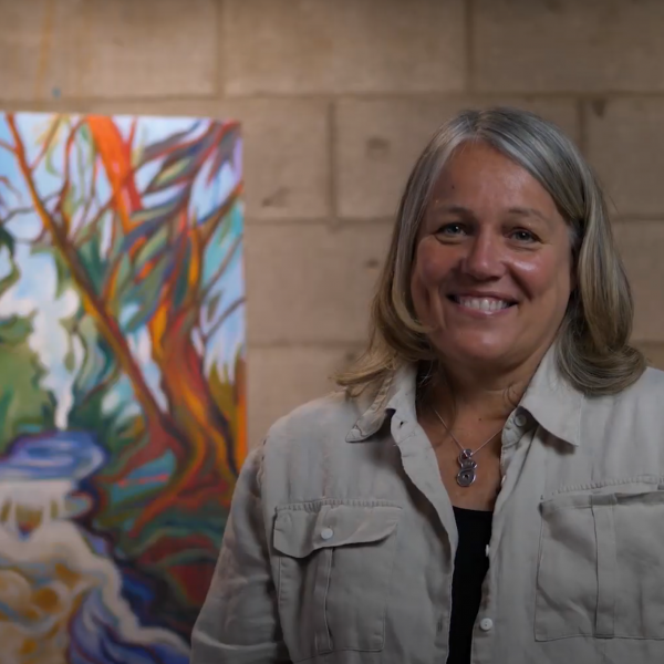 A photo of artist Helena Renwick sitting in front of her painting of a river.