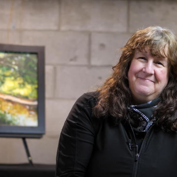 A photo of artist Janine Marson smiling with her painting in the background.