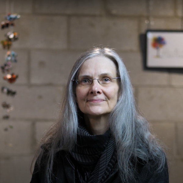 A photo of artist Michele Schwemmer sitting with her hanging mobile artwork in the background.