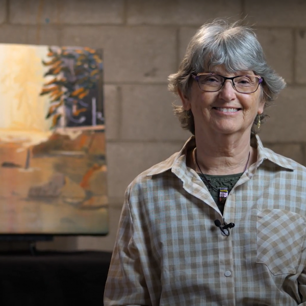 A photo of artist Pam Mackenzie smiling in front of her painting.