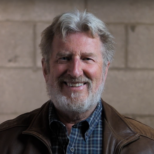 A smiling photo of artist Tom Clark.